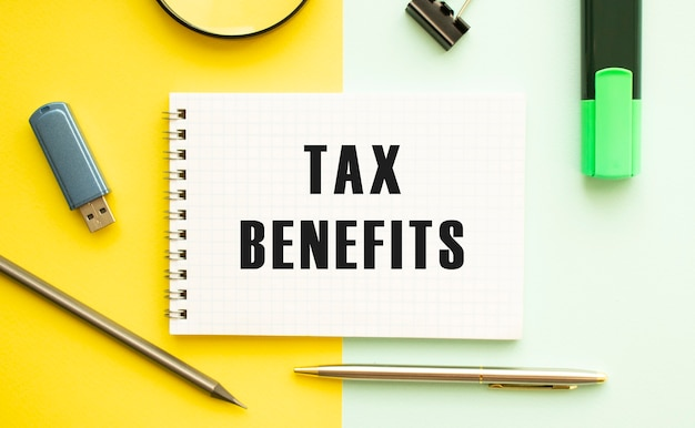 Блокнот с текстом налоговые пособие на офисном столе с канцелярскими принадлежностями