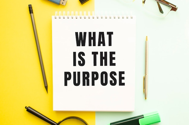Notebook with text what is the purpose on office table with office supplies