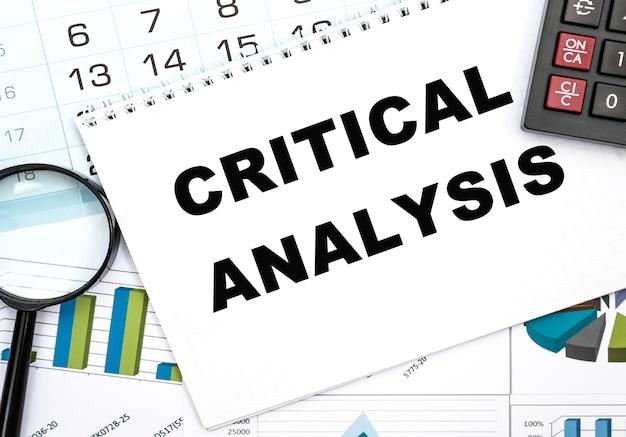 Блокнот с критическим анализом текста на офисном столе, документах, калькуляторе, очках и ручке