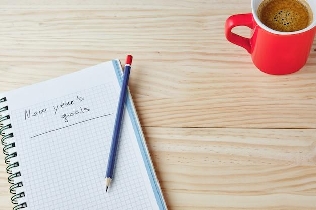 Блокнот со словами новогодние цели, написанные на фоне из натурального дерева с синим и красным карандашом сверху и красной чашкой кофе в углу