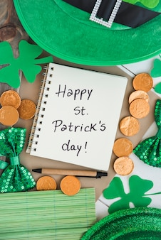 Notebook with title near coins, bow ties, saint patricks hats and decorative clovers