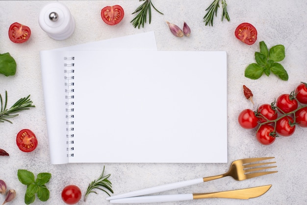 Notebook with tomatoes beside