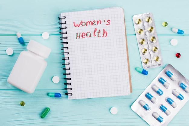 파란색 책상에 다양한 알약이 있는 노트북. 메모장에 여성의 건강 단어입니다.