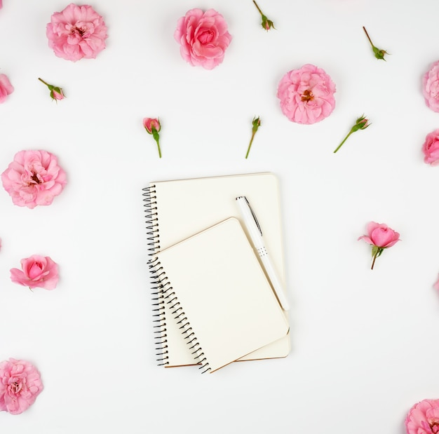 Notebook with white blank pages on purple and pink with petals