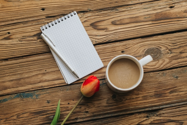 Блокнот с белыми страницами, серебряная ручка, один красный тюльпан на деревянном фоне. свободная область для текста. вид сверху