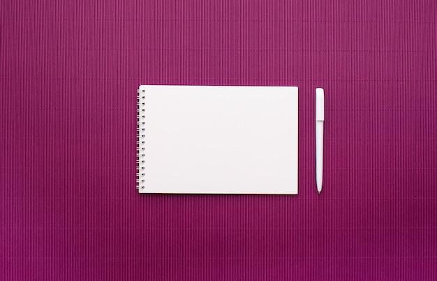 空のページ、白いペン、明るいライラックの背景を持つ春に白いシーツのノートブック。上から見て、テキストを配置します。フラットレイ