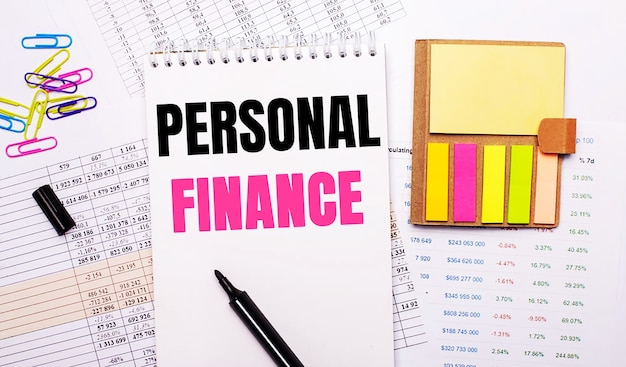 A notebook with the words personal finance, a marker, colored paper clips and bright note paper lie on the background of the graphs