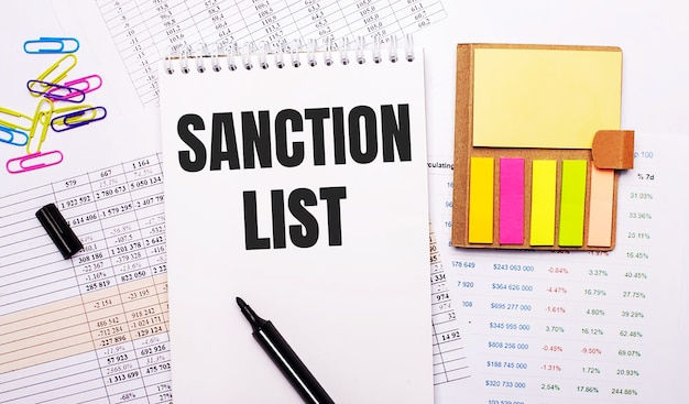 A notebook with the words sanction list, a marker, colored paper clips and bright note paper lie on the background of the graphs.