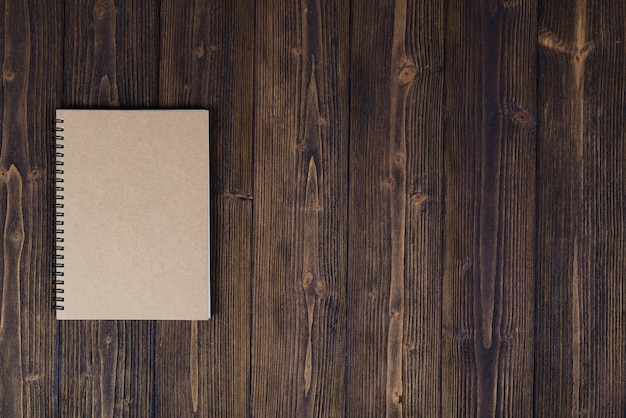 Notebook on wood table top view with copy space.