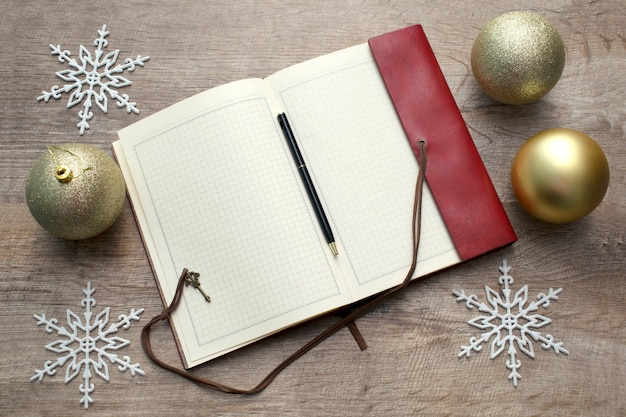 Notebook on wooden table, new year's decoration and christmas balls, copy space for notes.