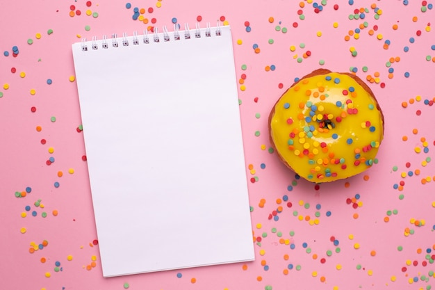 Notebook and yellow sweet donut on a pink background flat lay