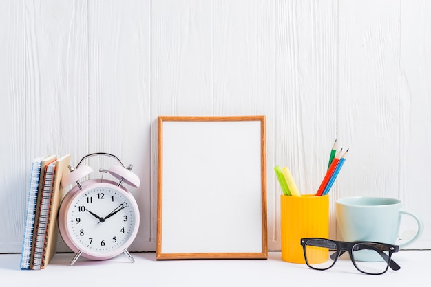 Notebooks; alarm clock; blank frame; pencils holder; cup and eyeglasses against white wooden wallpaper