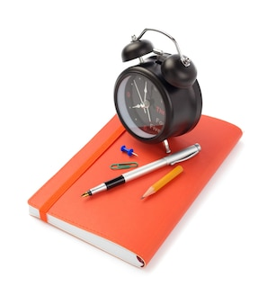 Notebooks and alarm clock isolated at white background