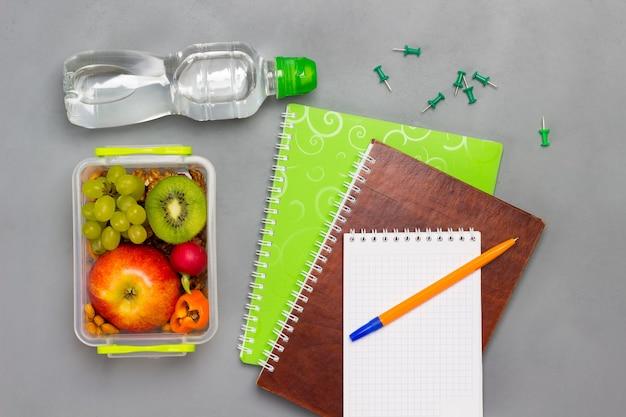 ノートとペン、フルーツとナッツの入ったお弁当箱、ボトル入り飲料水