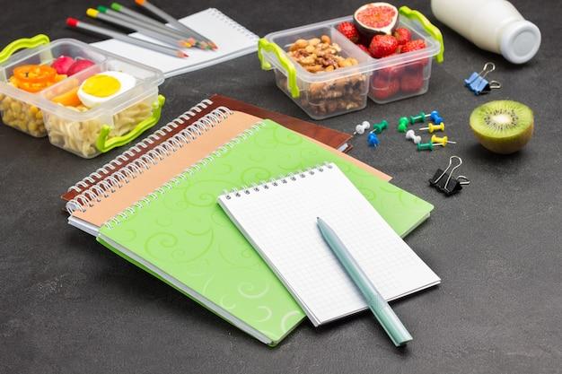 Блокноты и ручки, карандаши. школьный ящик с фруктами и орехами.