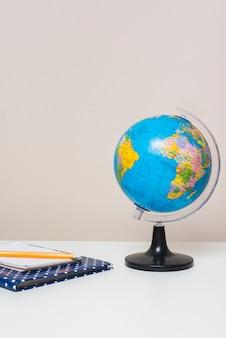 Ноутбуки и карандаш около земного шара
