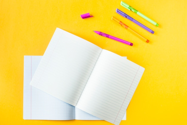 Notebooks in a box and in a line near to handles on a yellow background