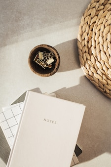 노트북, 나무 그릇에 클립, 짚 베이지 색 콘크리트 표면에 서