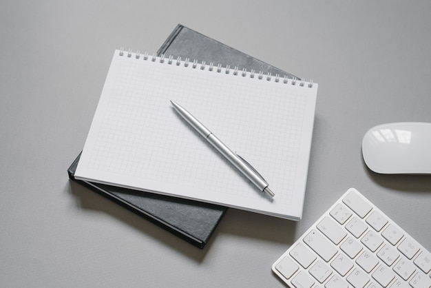 Notebooks or diaries with a blank page and a ballpoint pen on top of them. office worker's place