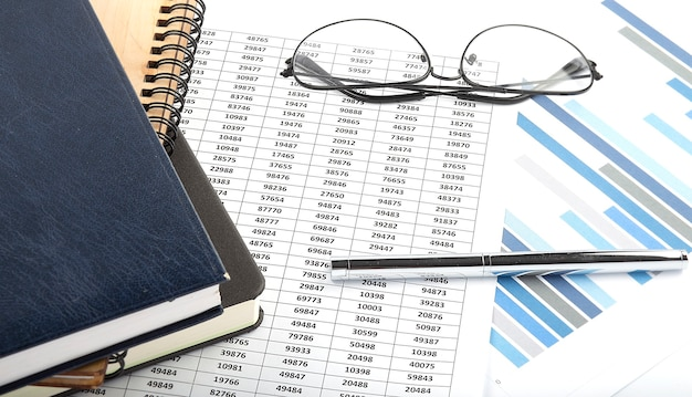 Notebooks on the financial charts with pen and glasses