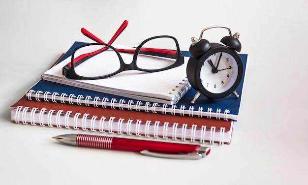 Блокноты, очки, ручка и часы. канцелярские товары для работы и учебы. копировать пространство