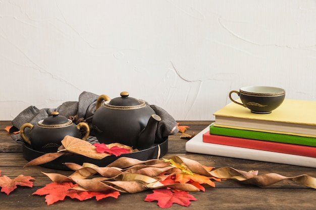 Notebooks and leaves near tea set