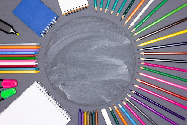 Notebooks markers colored pencils chalk stick with round chalkboard on desk children creativity