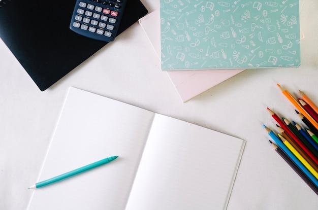 Notebooks near pencils and calculator