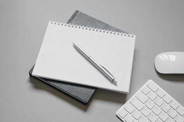 Блокноты или дневники с пустой страницей и шариковой ручкой поверх них. место офисного работника