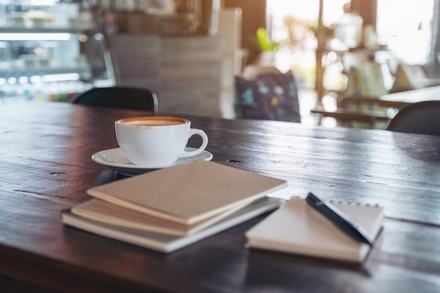 Notebooks, pen and coffee cup on wooden table