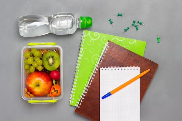 Notebooks and pen, lunch box with fruits and nuts and bottle of water