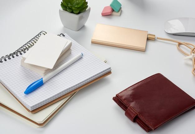 ノート、ペン、名刺のスタック、茶色の革の財布、コード付きのパワーバンク