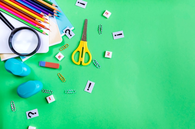 Notebooks, pencils, scissors and an eraser on green