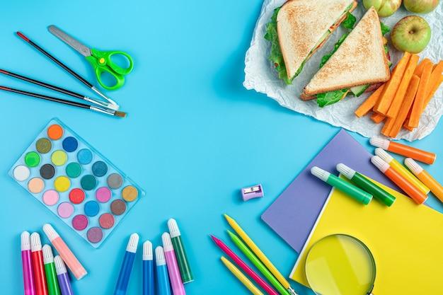 ノートブック、ペン、文房具、青い背景にサンドイッチ、リンゴ、ニンジンの朝食。上面図、コピースペース。学校に戻る。