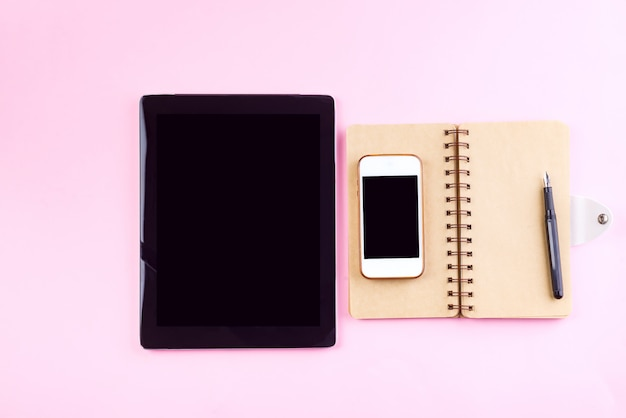 Notebooks, tablet, pen and smart phone on a pastel pink background