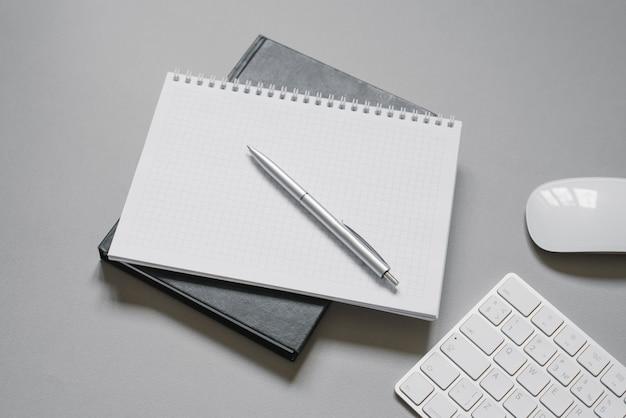 空白のページがあり、ハードウェアの近くにボールペンが付いているノートブック