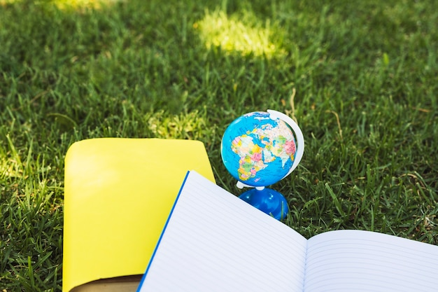 Notebooks with globe on grass