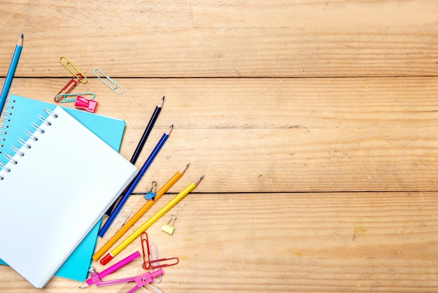 Notebooks with school supplies and stationery on the wooden table background