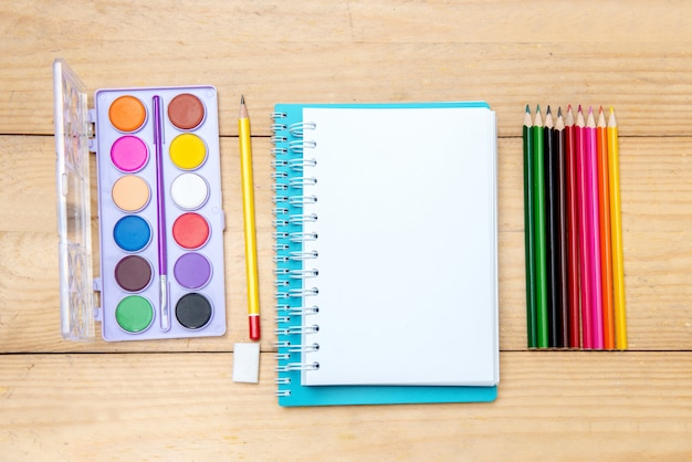 Notebooks with school supplies and stationery on the wooden table