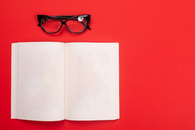 Noteboook and glasses isolated with copyspace on red Premium Photo