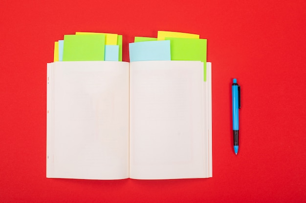 Noteboook and pen isolated on red background Premium Photo
