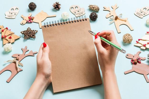 青の背景にnoteebokでいくつかのノートを作る女性の手の上から見る