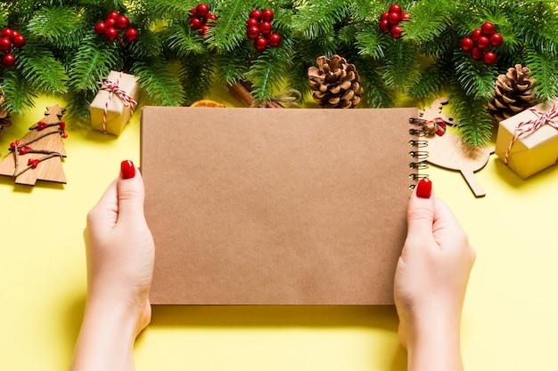 黄色のnoteebokでいくつかのノートを作る女性の手の上から見る。正月飾りとおもちゃ。