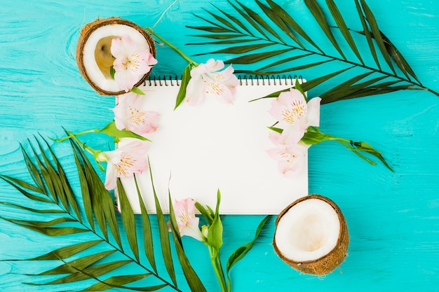 Notepad among plant leaves with fresh coconuts and blooms
