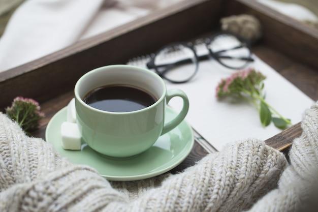 Блокнот и чашка кофе на подносе