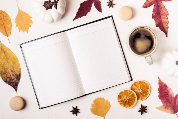 Блокнот и чашка кофе на белом столе с узором из осенних листьев.