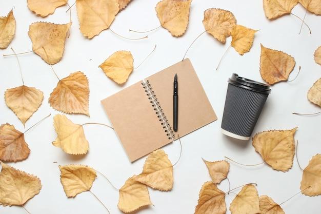 メモ帳と一杯のコーヒーと落ち葉。ジャーナリズムの概念、トップビュー。