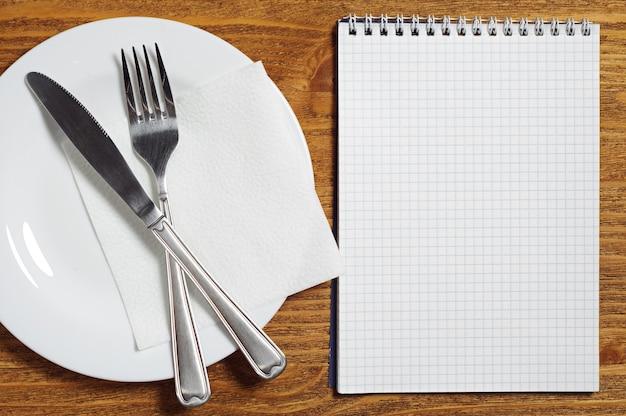 メモ帳とカトラリー。カフェやレストランのメニューのテンプレートとして使用できます