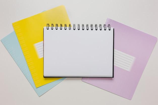 机の上のメモ帳と練習帳。白い背景のコピースペースオフィスでモックアップ。学校に戻る