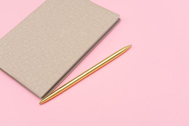 Блокнот и золотая ручка на розовом фоне, макет сверху, копия пространства, концепция цветных блоков